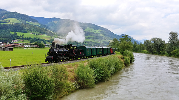 steam train by a river